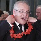 Prime Minister Scott Morrison and wife Jenny don garlands as they arrive at the Midwinter Ball.