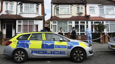 Police officers attend the scene where a women who was around eight months pregnant was stabbed to death in Croydon, south London.