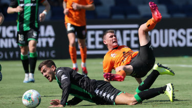 On the slide: Jerry Skotadis of Western United FC upends Corey Brown of Brisbane Roar.