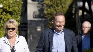 Former prime minister Tony Abbott strolls along the Rose Bay pier with Teena McQueen.