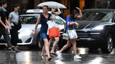 Pedestrians are seen in the CBD during a thunderstorm in Sydney.