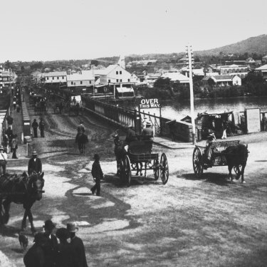 Horse drawn carraiges and pedestrians at the northern approach of the first permanent Victoria Bridge, ca 1885.