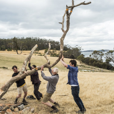 Kevin Perkins (second from right) and helpers affix an old tree to a stump, which will serve as the setting for 12 whittled bird sculptures.