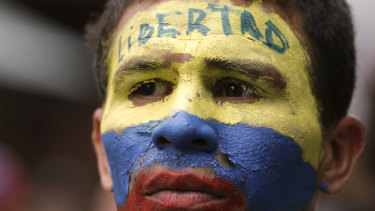 "An opponent to President Nicolas Maduro, his face the colours of the Venezuelan national flag and the word for ""Freedom"" written on his forehead, takes part in a march in Caracas on Saturday."