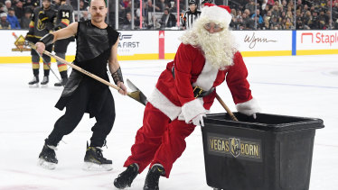 Members of the Knights Guard, including one wearing a Santa Claus outfit, clean the ice during the Vegas Golden Knights' game against the Colorado Avalanche on Monday.