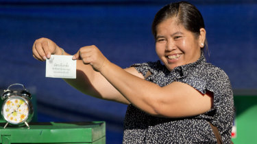 A Thai voter with a ballot paper in her hand, poses at a polling station in Bangkok, Thailand, on Sunday.