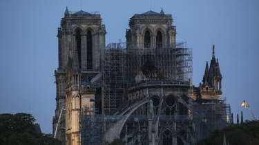 Firefighters operate on the Notre-Dame Cathedral after the fire in Paris.