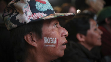 A supporter of presidential candidate Andres Manuel Lopez Obrador with the MORENA party letters painted on his cheek, celebrates Lopez Obrador's victory, in Mexico City's Alameda Central Park, on Sunday.