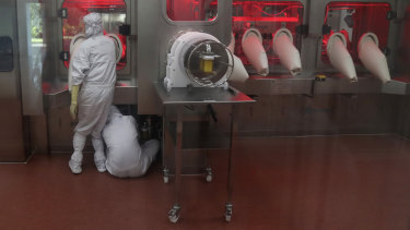 Employees operate a filling machine inside a laboratory at the Serum Institute of India in Pune, India.