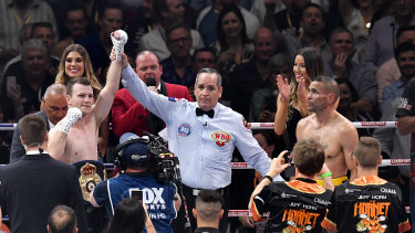 The victor and the vanquished: Anthony Mundine watches on as Jeff Horn takes the limelight on Friday night.