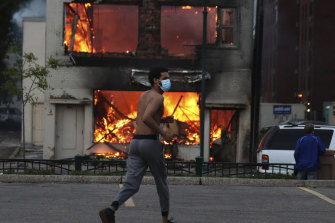 A man runs near a burning building after a night of unrest in downtown Minneapolis.