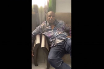 Guinean President Alpha Conde sits on a sofa in an unknown location.