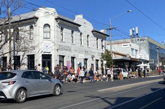 People congregate outside the Peacock Inn, on High Street in Northcote, on Sunday.
