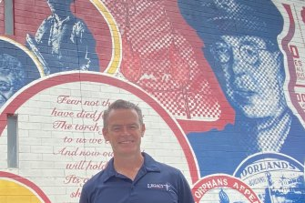 Legacy Queensland chief executive Brendan Cox in front of a mural of Legacy founder Stan Savage, an army officer from WWI and WWII.