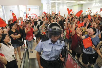 Pro-China supporters cheer after riot police arrived at the Kowloon Bay district in Hong Kong.