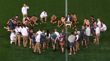 Brisbane players and staff pause for a beer on the Suncorp surface to mark the end of their season.