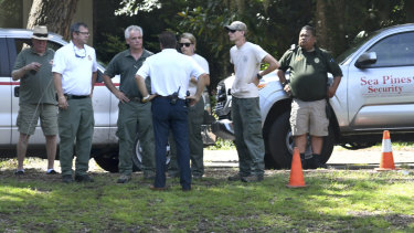 Law enforcement officials stand near where authorities say Cassandra Cline was dragged into a lagoon by an alligator and killed while trying to save her dog on Monday on Hilton Head Island, South Carolina.