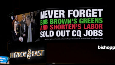 An electronic billboard in the middle of Rockhampton raises the spectre of Julia Gillard and Bob Brown.