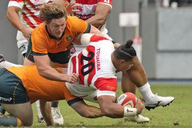 Australia's Michael Hooper tackles Japan's Tevita Tatafu during a rugby international match between the Wallabies and Japan in Oita, Japan, Saturday, Oct. 23, 2021. (Kyodo News via AP)