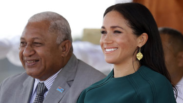 Meghan, Duchess of Sussex, smiles as she sits with Fiji's Prime Minister Frank Bainimarama.