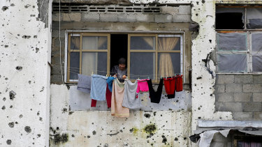 A Palestinian woman hangs clothes in a damaged apartment block, which was partially destroyed during the 2014 war between Israel and Hamas, in Beit Lahiya, Gaza Strip.