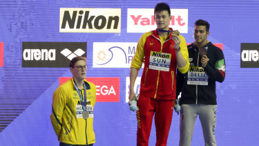 China's Sun Yang, centre, with his gold medal as silver medallist Australia's Mack Horton, left, stands away from the podium.