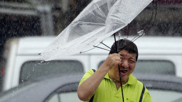 A Taiwanese man holds an umbrella against powerful gusts of wind generated by typhoon Lekima in Taipei, Taiwan.