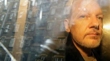 Buildings are reflected in the window as WikiLeaks founder Julian Assange is taken from court.