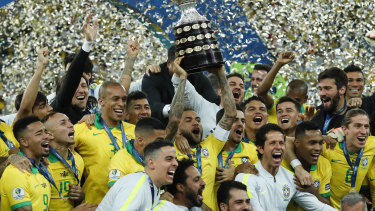 Heroes' salute: Brazil's Dani Alves lifts up the trophy after winning the final of the Copa America against Peru at the Maracana stadium in Rio de Janeiro.