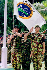 February 14, 2000: Soldiers salute the INTERFET flag as they are relieved by United Nations forces in Dili, capital of East Timor.