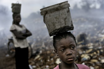 In Ghana, West Africa, Fati, 8, works with other children searching through hazardous waste.