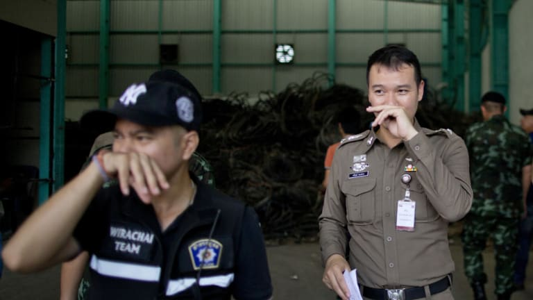 Thai police officers hold their noses to avoid inhaling a strong odor generated in Camellia Corporation, an e-waste processing factory in Bangkok.