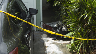 Debris lies on the ground where parts of a helicopter hit a parked car