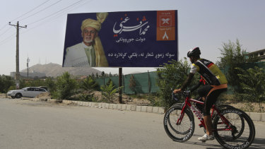 Afghan men cycle past an election poster of presidential candidate Ashraf Ghani in Kabul.