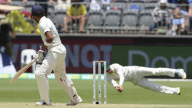Pivotal moment: Virat Kohli looks behind to watch Peter Handscomb take a catch ruled to be legitimate.