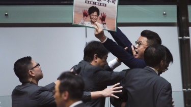 A pro-democracy politician is taken away as he shouts a slogan while Hong Kong Chief Executive Carrie Lam arrives at chamber of the Legislative Council on Thursday.