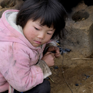 Xia Zhongmei sits at an outdoor furnace in Shanqiao, a village in China's Yunnan province.