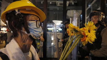 Hong Kong protesters defy police, deface Beijing office during march