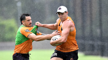 Corey Oates pushes away from the defence of Jack Bird at a soaked training session on Monday.