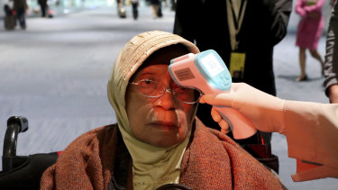 A health official scans the body temperature of a passenger at Jakarta's Soekarno-Hatta International Airport.