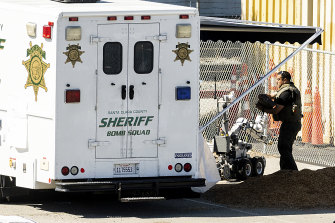 An emergency responder stows a bomb squad robot following the shooting in San Jose.
