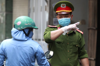 A police officer talks to a woman at the barricaded entrance of an alley where one of its residents is suspected to have COVID-19 in Hanoi, Vietnam.