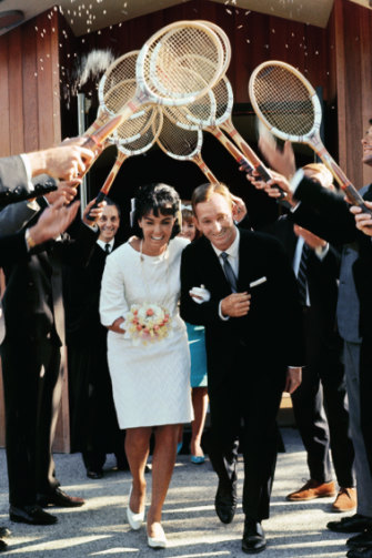 Rod Laver and Mary Benson pass through an arch of tennis racquets after their marriage in 1966.