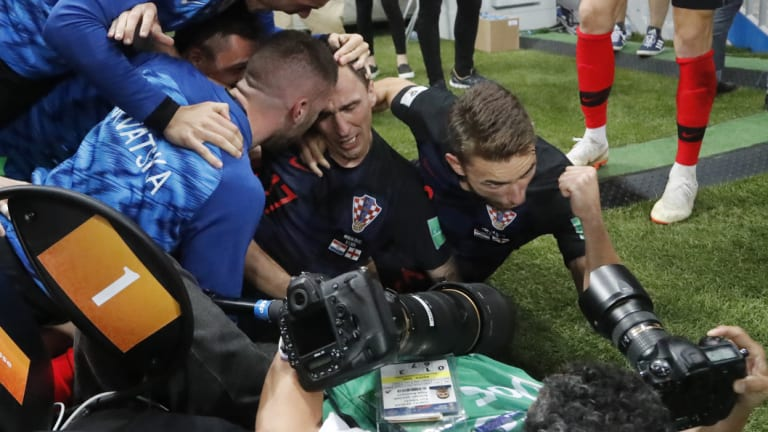 Croatia's Mario Mandzukic, centre, sits on the ground after he fell over photographer Yuri Cortez, who is in the foreground still taking photos.