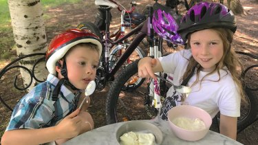Tim's eight-year-old daughter Emily (right) and her five-year-old cousin Lachlan Hartmann enjoy an ice cream break while riding around Yarralumla.