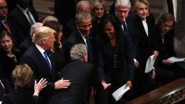 Former president George W. Bush shares a joke with Michelle Obama.