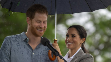 Dream team: Meghan shelters Prince Harry while he speaks at a community picnic.