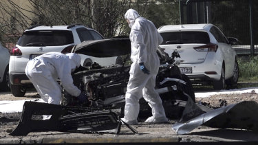 Forensic experts examine the scene of the blast in the upscale Glyfada area .