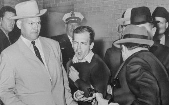 Detective Jim Leavelle (left) escorts Lee Harvey Oswald as Dallas nightclub owner Jack Ruby, foreground, shoots Oswald from point-blank range in a corridor of Dallas police headquarters, 1963.