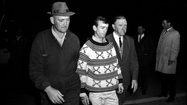 The Police Commissioner, Mr. Norman Allan (right), walks beside Wally Mellish at the Ingleburn Army Camp after his surrender